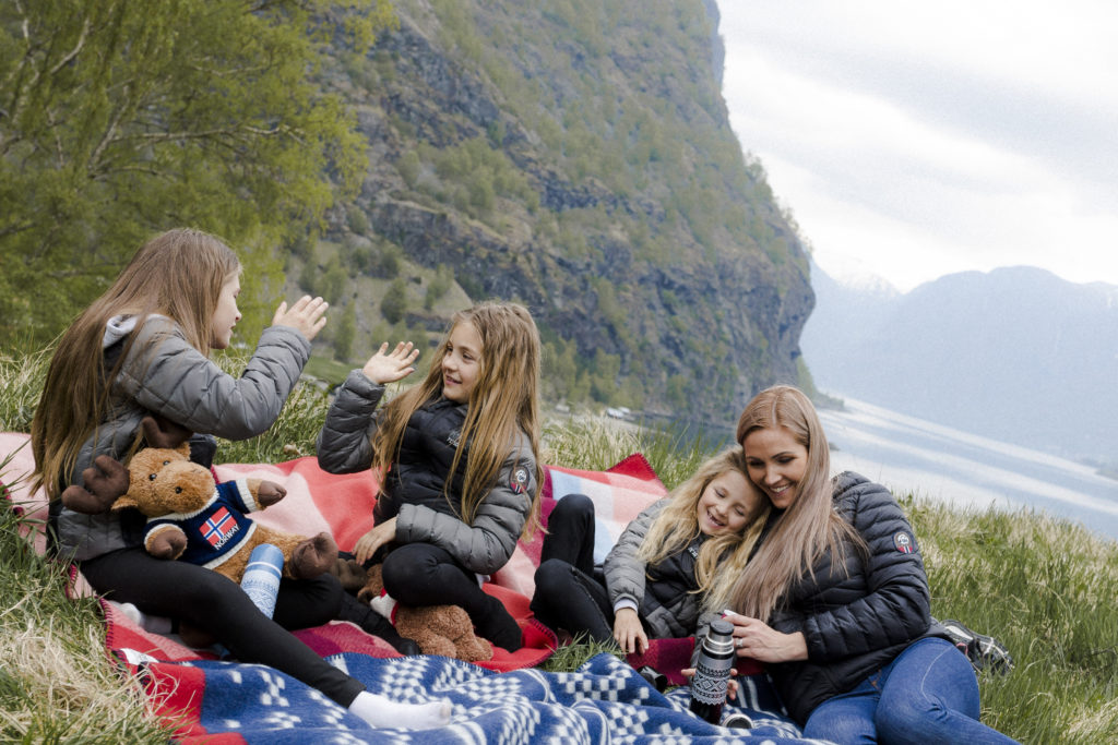 Norwegian family having lunch by the fjords wearing down jackets